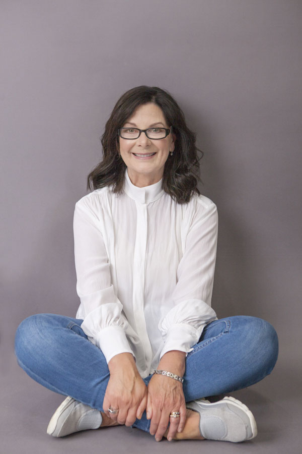The Adelaide author sits on the floor cross legged with classic white shirt and blue jeans
